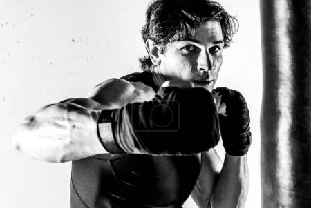 Photo for Black and white photo of muscular kickbox fighter punching - Royalty Free Image