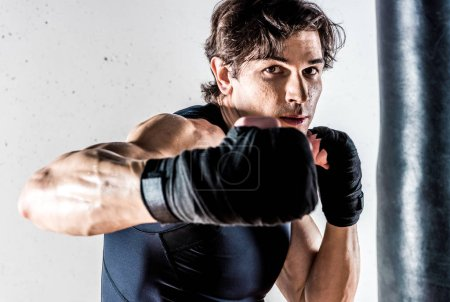 Photo for Muscular kickbox fighter punching while looking at camera on white - Royalty Free Image