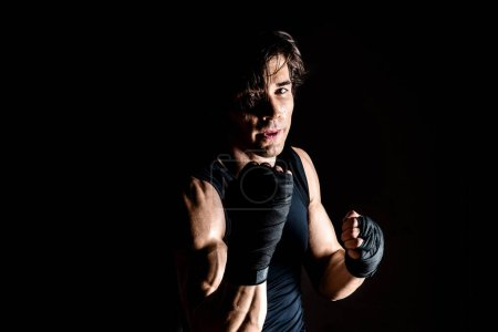 Photo for Muscular kickbox fighter punching while looking at camera on black - Royalty Free Image