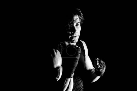 Photo for Black and white photo of muscular kickbox fighter punching while looking at camera - Royalty Free Image