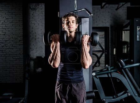 Photo for Young concentrated sportive man exercising with dumbbells in gym - Royalty Free Image
