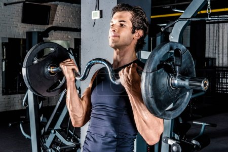 Photo for Young sportive man exercising with barbell in gym - Royalty Free Image