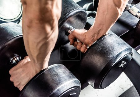 Photo for Close-up partial view of young man holding two dumbbells in gym - Royalty Free Image
