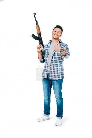 Photo pour Souriant jeune homme afro-américain tenant fusil et montrant le pouce en haut isolé sur blanc - image libre de droit