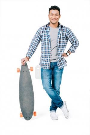 Photo pour Beau jeune homme africain-américain tenant skateboard et souriant à la caméra isolé sur blanc - image libre de droit