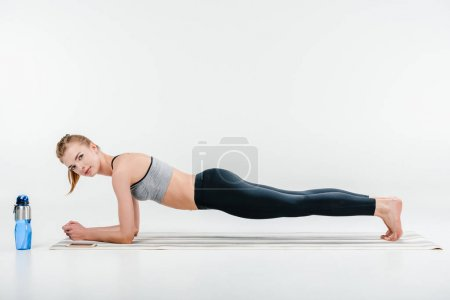 Beautiful fit young girl doing plank exercise...