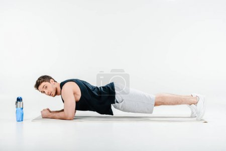 Handsome young man standing plank isolated on whit...