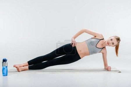 Photo pour Séduisante jeune fille fit faire exercice planche latérale - image libre de droit