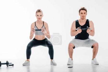 couple doing squats with dumbbells