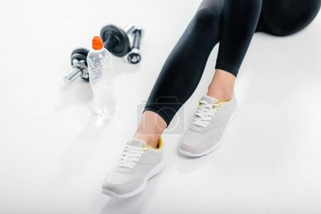 woman in sneakers with fitness equipment