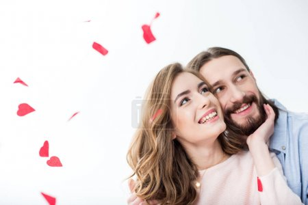 Photo for Beautiful smiling couple in love looking up on white with red falling hearts isolated on white - Royalty Free Image