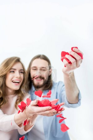 Photo for Beautiful happy couple in love holding red paper hearts in hands isolated on white - Royalty Free Image