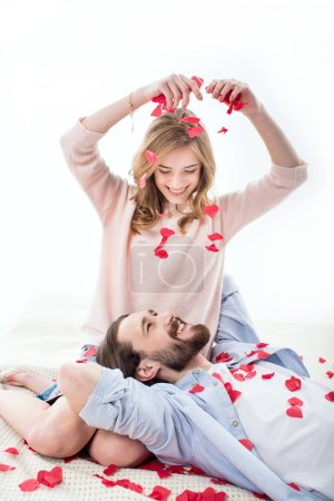 Photo for Beautiful couple in love smiling and playing with red paper hearts isolated on white - Royalty Free Image