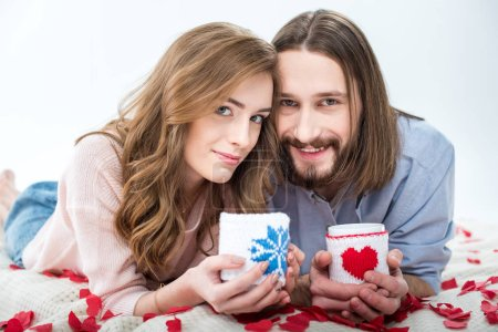 Photo for Beautiful couple in love holding cups and smiling at camera isolated on white - Royalty Free Image