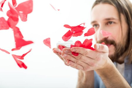 Man blowing paper hearts