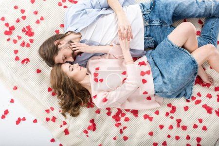 Photo for Beautiful couple in love lying and touching each other on red paper hearts - Royalty Free Image