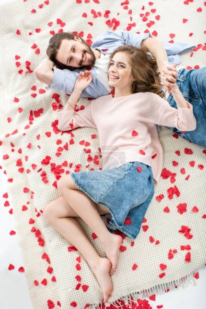 Photo for Beautiful young couple in love lying together and smiling - Royalty Free Image