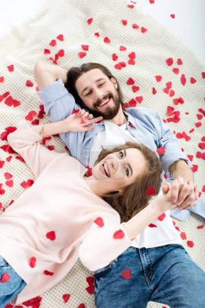 Photo for Beautiful young couple in love lying together and smiling on red paper hearts - Royalty Free Image