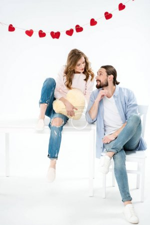 Photo for Beautiful young couple in love sitting and looking at each other isolated on white - Royalty Free Image