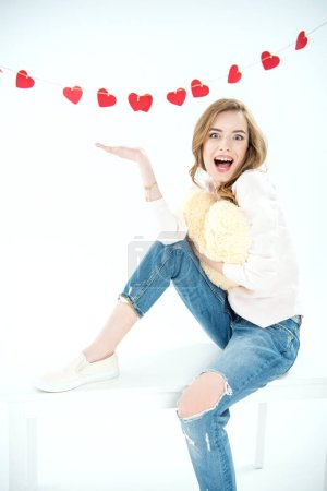 Photo pour Surprised young woman with heart shaped pillow looking at camera isolated on white - image libre de droit