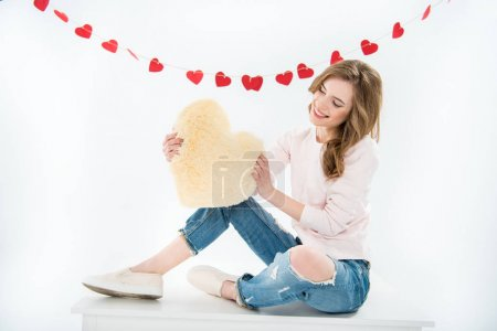 Photo for Beautiful smiling woman sitting and holding heart shaped pillow isolated on white - Royalty Free Image