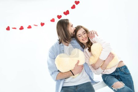 Photo for Beautiful young couple in love sitting together and hugging heart shaped pillows isolated on white - Royalty Free Image