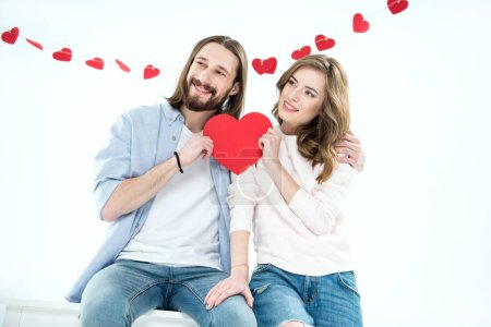 Photo for Young happy couple in love holding red paper heart and looking away isolated on white - Royalty Free Image
