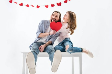 Photo for Young happy couple in love holding red paper heart and sitting on table isolated on white - Royalty Free Image