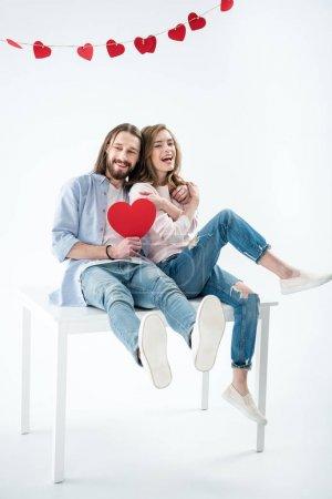 Photo pour Jeune couple heureux amoureux tenant coeur de papier rouge et assis sur la table isolé sur blanc - image libre de droit
