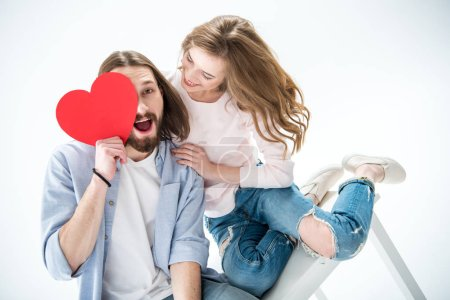 Photo for Young happy couple in love holding red paper heart and sitting on table - Royalty Free Image