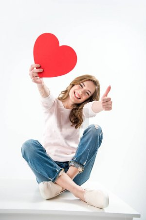 Photo for Young happy woman with red paper heart shows thump up isolated on white - Royalty Free Image
