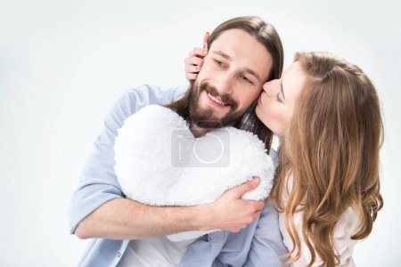 Photo for Young woman kissing man who holding heart shaped pillow - Royalty Free Image