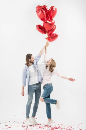 Photo pour Young couple holding heart shaped air balloons isolated on white - image libre de droit