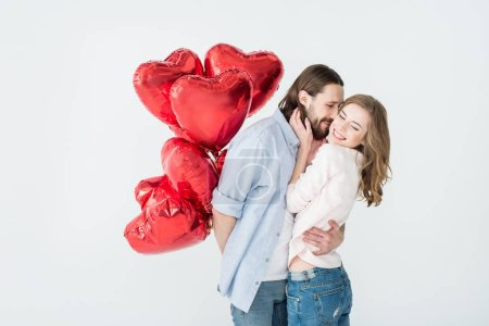 Photo pour Young couple holding heart shaped air balloons and embracing isolated on white - image libre de droit