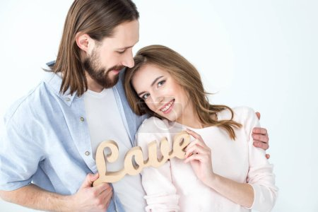 Photo for Young beautiful couple holding wooden word love and smiling isolated on white - Royalty Free Image