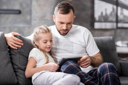 Photo for Father and daughter sitting on grey sofa and using digital tablet - Royalty Free Image