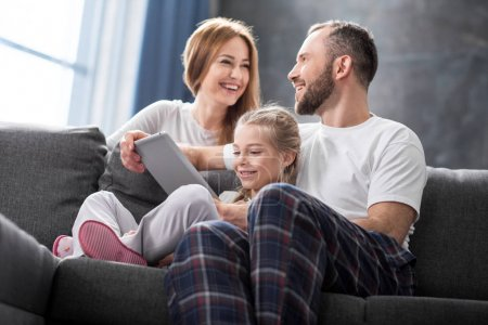 Photo for Happy family sitting on sofa and using digital tablet - Royalty Free Image