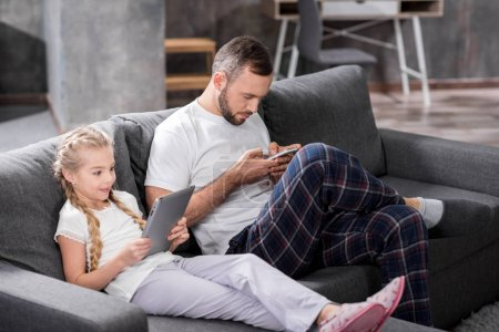 Photo for Father and daughter sitting on grey sofa and using digital devices - Royalty Free Image