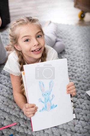 Photo for Cute smiling girl showing funny drawing and looking at camera - Royalty Free Image