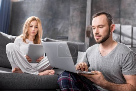 Photo for Upset young couple using digital devices at home - Royalty Free Image