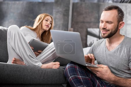 Photo for Smiling young couple using digital devices at home - Royalty Free Image