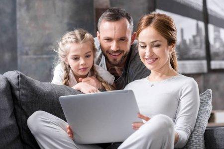 Photo pour Souriant jeune famille utilisant ordinateur portable ensemble à la maison - image libre de droit