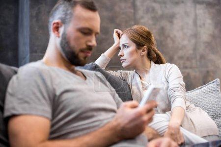Photo pour Jeune homme à l'aide de smartphone tandis que sa copine pensive assis avec lui sur le canapé - image libre de droit