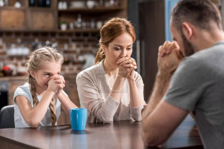 Photo for Young family praying while sitting at the table in kitchen - Royalty Free Image