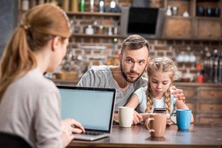 Photo pour Jeune famille dans la cuisine utilisant des appareils et boire du thé ou du café - image libre de droit