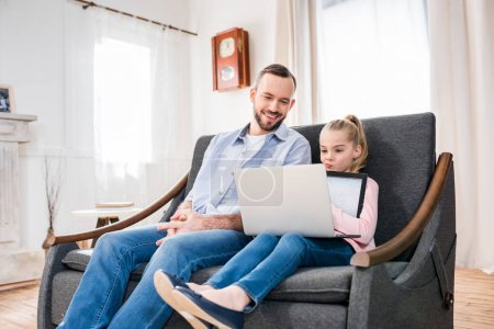 Photo for Smiling father and cute little daughter using laptop together at home - Royalty Free Image