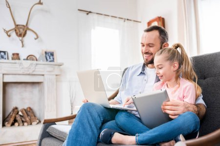 Father and daughter using devices
