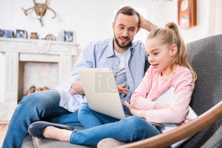 Photo pour Souriant père et fille en utilisant ordinateur portable ensemble - image libre de droit
