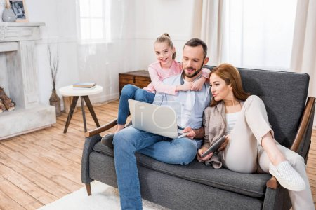 Photo for Smiling family sitting on grey couch and using laptop - Royalty Free Image