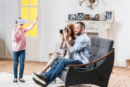 Photo for Happy family using virtual reality headsets together at home - Royalty Free Image